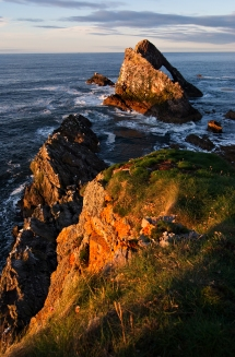 Bow Fiddle Rock, a large rock about 50 feet high just off the coast. The quartzite rock has a large sea arch, which somewhat resembles the bow of a fiddle.