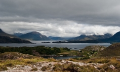 The Torridon hills as viewed from near Ardheslaig ~ Liathach which dominates the skyline here is one of the most famous of the Torridon Hills. At a height of 3,140 feet (957 m), it lies to the north of the A896 road, in the Northwest Highlands of Scotland, and has two peaks of Munro status: Spidean a' Choire Lèith at the east of the main ridge, and Mullach an Rathain at the western end of the mountain. The name Liathach is pronounced [ˈʎiə.əx] in Scottish Gaelic, and means 'The grey one'. Liathach conveys an aura of impregnability when seen from the roadside below, as the slopes appear to rise up in a series of near vertical rocky terraces