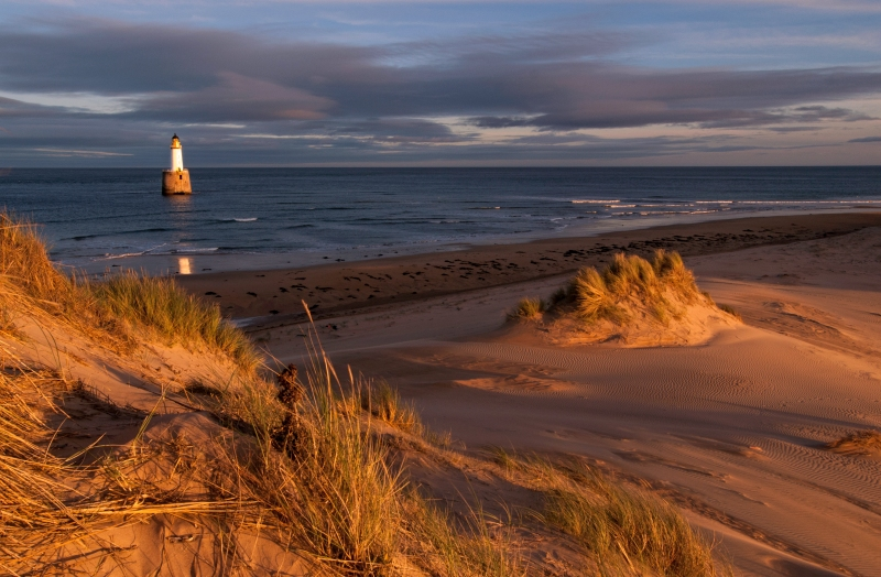 Rattray Point, is a headland in Buchan, Aberdeenshire, on the north-east coast of Scotland. The dunes at Rattray Head beach can be up to 75 feet (23 m) high and stretch 17 miles (27 km) from St Combs to Peterhead. The 120 feet (37 m) Lighthouse  was built in 1895 by the engineering brothers  Stevenson David Alan Stevenson and Charles Alexander Stevenson. In February 1982 it became unmanned and self-working.[2][3] The lighthouse is accessible by way of a causeway that is usually underwater being only visible at low tide. It is wide enough for a vehicle to cross. Remains of several shipwrecks can still be seen on the beach. (wikipedia)