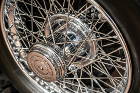 A close Up Detail of a classic Rolls Royce spoke racing wheel with lots of reflections.